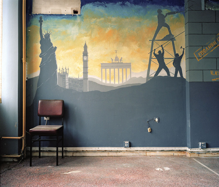 """'In Waiting,' is an examination of Athens and its role as a physical stage for the economic crisis. Primarily, I am exploring the interiors of government buildings, institutions, and schools to question how these spaces reflect modern Greek culture and character.Spaces, which once seemed banal or unimportant, now reveal nuances of Greek reality and have social and political implications.  Mural """"Sold"""". Former building of Ministry of Employment"""